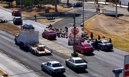 Automovilistas y transeúntes apoyan a levantar mercancía que cayó de un tráiler